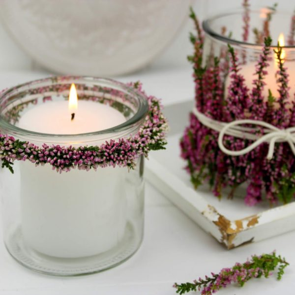 Windlichter und Blumenkränze mit Heidekraut an einem Windlicht