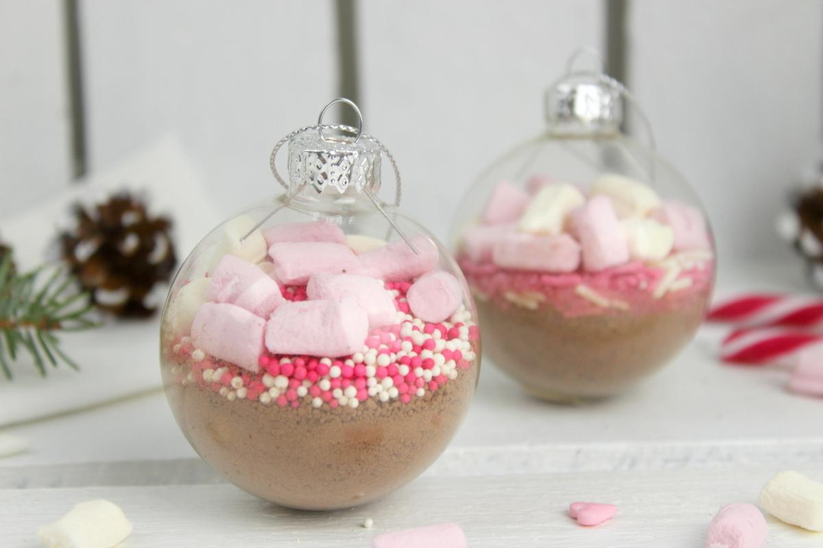 Trinkschokolade mit bunten Streuseln, Zuckerstange und Marshmallows in einer Christbaumkugel