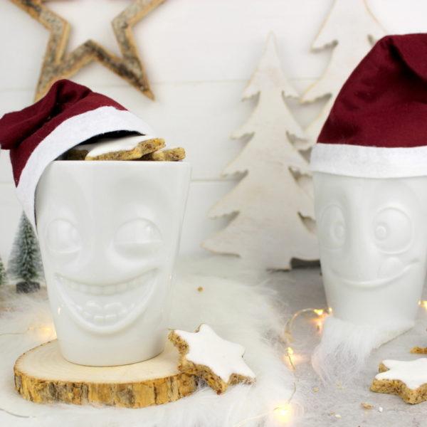 lustige Tassen mit Weihnachtsmannmützen gefüllt mit Zimtsternen