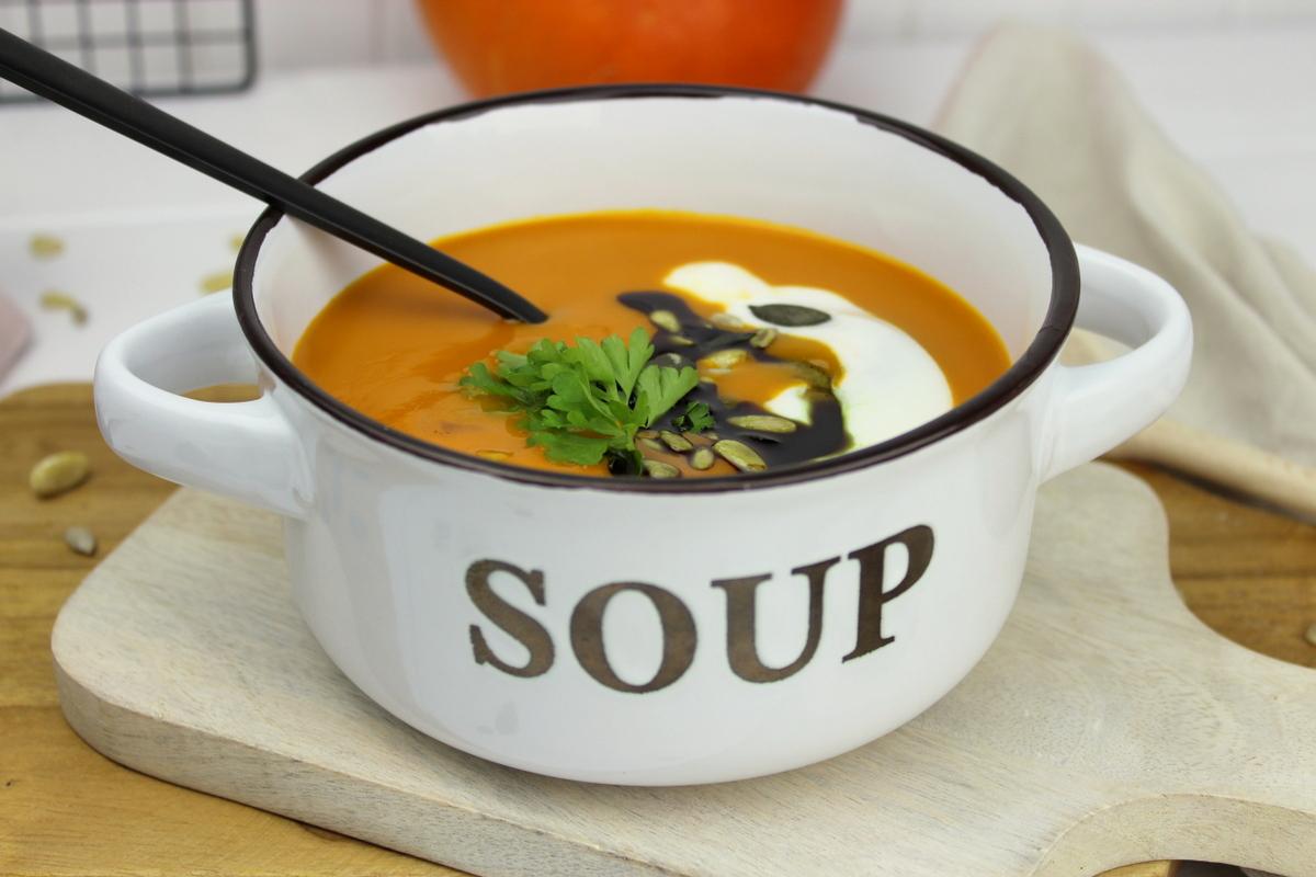 Kürbissuppe mit Hokkaido, Möhren und Kokosmilch serviert mit Petersilie, Kürbiskernen und Kürbisöl